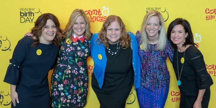 The Healthy Birth Day, Inc. Founders stand in front of a yellow backdrop