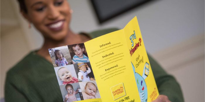 Black woman reads bright yellow Count the Kicks brochure