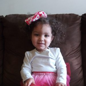 Baby save Nevaeh sits on a couch wearing a pink skirt and pink bow