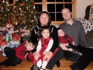 Mylynn Tufte sits in front of her Christmas tree with her three children and her husband