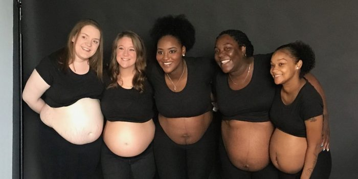 A diverse group of expectant moms smile for a group photo