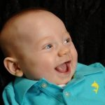 Baby Save Cooper smiles and wears a light blue polo shirt