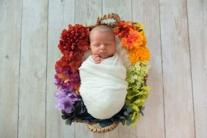 A baby swaddled in a white blanket sleeps in a nest of colorful flowers