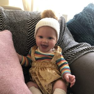 Smiling, happy baby wearing a hat sits on a couch