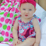 Baby Save Lincoln wears a bright pink dress and pink headband