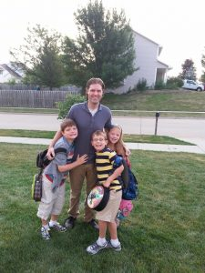 Luke Morlan stands with his three living children,