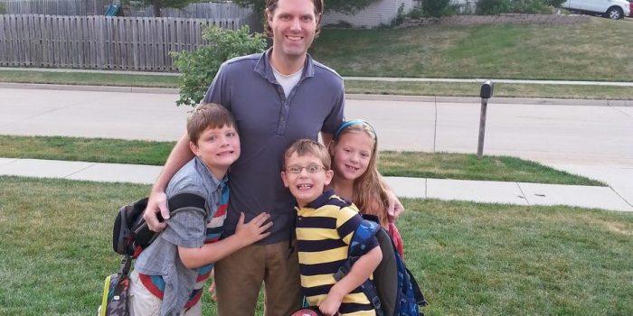 Luke Morlan stands with his three living children,