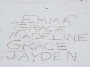 The names of the founders daughters carved in the sand on a beach