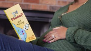 An expectant mom reads a Count the Kicks brochure.