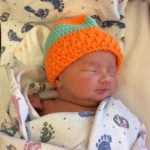 Baby Save Aiden wearing an orange hat.