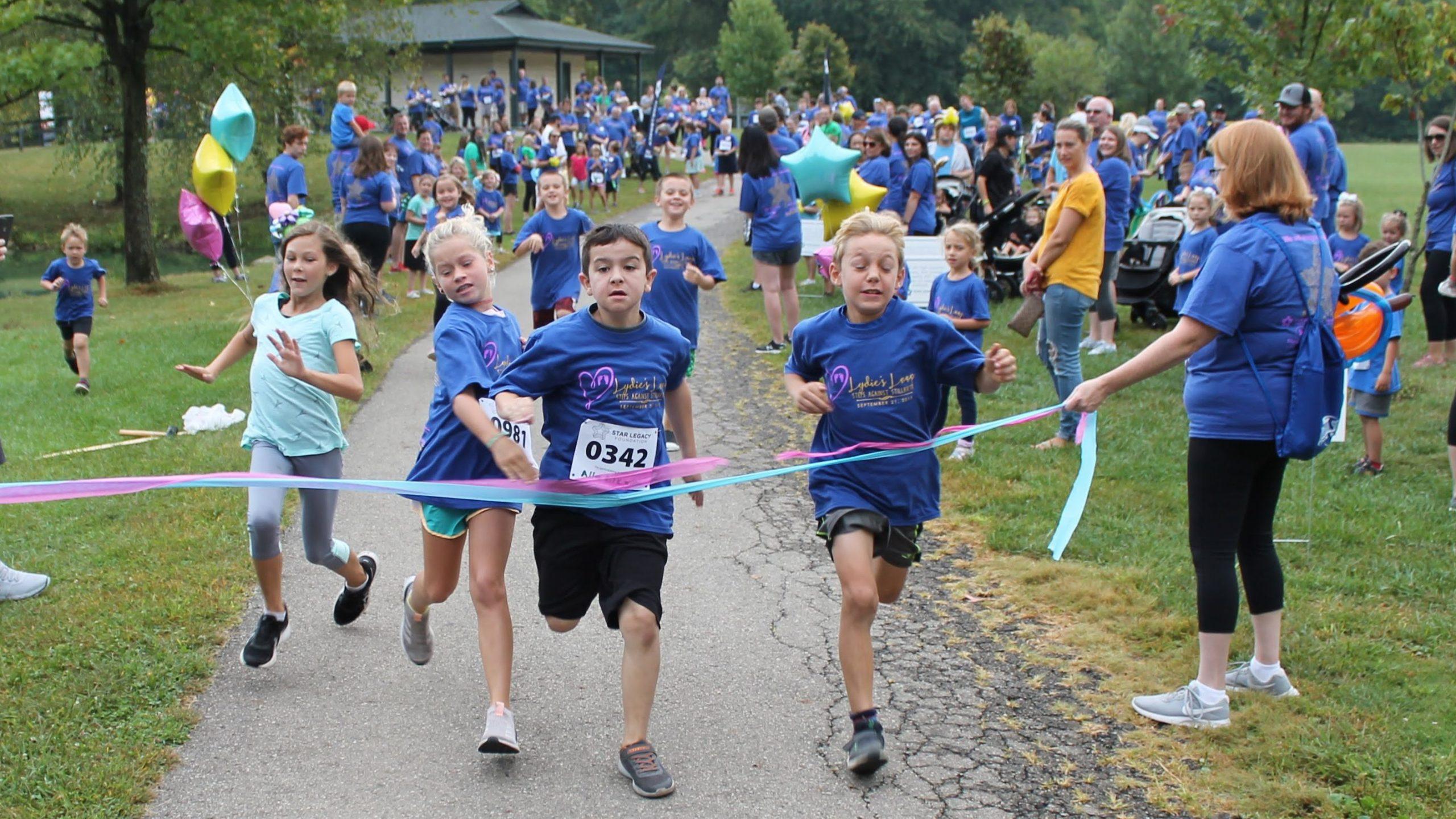 Kids cross the finish line at Lydie's Loop kids race